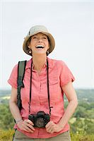 Happy woman with camera Stock Photo - Premium Royalty-Freenull, Code: 6114-06610311