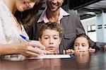 Family signing into hotel Stock Photo - Premium Royalty-Free, Artist: Blend Images, Code: 6114-06610506