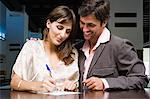 Couple signing into hotel Stock Photo - Premium Royalty-Free, Artist: Cultura RM, Code: 6114-06610509