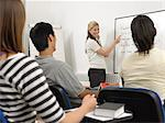 Teacher writing on whiteboard Stock Photo - Premium Royalty-Free, Artist: Blend Images, Code: 6114-06610569