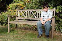 sad child sitting - Sullen boy on a bench Stock Photo - Premium Royalty-Freenull, Code: 6114-06610618