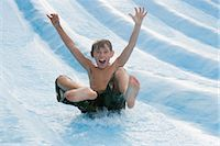Boy on a water slide Stock Photo - Premium Royalty-Freenull, Code: 6114-06610661