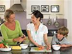 Exchange student preparing food with mother and son Stock Photo - Premium Royalty-Free, Artist: GreatStock, Code: 6114-06610777