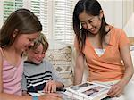 Children and exchange student looking at photo album Stock Photo - Premium Royalty-Free, Artist: AWL Images, Code: 6114-06610787