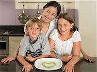 Young woman and children in kitchen Stock Photo - Premium Royalty-Freenull, Code: 6114-06610806