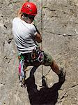Young man abseiling down cliff Stock Photo - Premium Royalty-Free, Artist: Cultura RM, Code: 6114-06610852
