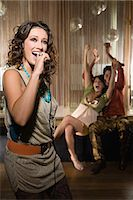 Young woman doing karaoke Stock Photo - Premium Royalty-Freenull, Code: 6114-06610945