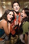 Friends doing karaoke Stock Photo - Premium Royalty-Free, Artist: Westend61, Code: 6114-06610946
