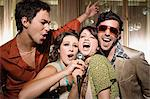 Friends doing karaoke Stock Photo - Premium Royalty-Free, Artist: Blend Images, Code: 6114-06610948