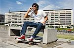 Young man with skateboard on cellphone Stock Photo - Premium Royalty-Free, Artist: CulturaRM, Code: 6114-06611261