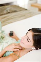Woman listening to music Stock Photo - Premium Royalty-Freenull, Code: 6114-06611792