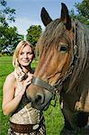 Young woman stroking a horse Stock Photo - Premium Royalty-Free, Artist: ableimages, Code: 6114-06611848