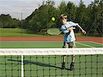 Boy playing tennis Stock Photo - Premium Royalty-Free, Artist: Blend Images, Code: 6114-06611886