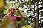 Man with binoculars in forest Stock Photo - Premium Royalty-Free, Artist: Ikon Images, Code: 6114-06611915