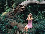 Woman in forest covering her eyes Stock Photo - Premium Royalty-Free, Artist: Blend Images, Code: 6114-06612040