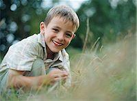 Boy crouching in grass Stock Photo - Premium Royalty-Freenull, Code: 6114-06612074