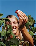 Woman holding a raspberry Stock Photo - Premium Royalty-Free, Artist: Cultura RM, Code: 6114-06612100