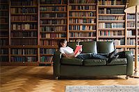 Girl reading on a sofa in the library Stock Photo - Premium Royalty-Freenull, Code: 6114-06612163