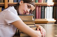 Girl hugging a pile of books Stock Photo - Premium Royalty-Freenull, Code: 6114-06612183