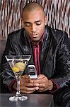 Man with cell phone and martini Stock Photo - Premium Royalty-Free, Artist: Glowimages, Code: 6114-06612476