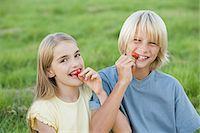 preteen long hair - Boy and girl eating strawberries Stock Photo - Premium Royalty-Freenull, Code: 6114-06612555