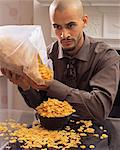 Man spilling cornflakes Stock Photo - Premium Royalty-Free, Artist: Blend Images, Code: 6114-06612683
