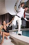 Woman pushing waiter into swimming pool Stock Photo - Premium Royalty-Free, Artist: Cultura RM, Code: 6114-06612736