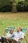 Couple relaxing in deckchairs in park Stock Photo - Premium Royalty-Free, Artist: ableimages, Code: 6114-06613055