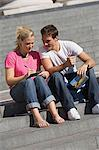Couple writing postcards on steps Stock Photo - Premium Royalty-Free, Artist: ableimages, Code: 6114-06613093