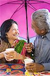 Couple under umbrella with cups of tea Stock Photo - Premium Royalty-Free, Artist: Russell Monk, Code: 6114-06613192