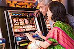 Couple playing on fruit machine Stock Photo - Premium Royalty-Free, Artist: Robert Harding Images, Code: 6114-06613193