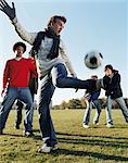 Men playing football in park Stock Photo - Premium Royalty-Free, Artist: Christina Handley, Code: 6114-06613256
