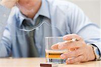 Man drinking whisky and smoking Stock Photo - Premium Royalty-Freenull, Code: 6114-06613285