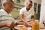 Father and son in eating in kitchen Stock Photo - Premium Royalty-Free, Artist: Photocuisine, Code: 6114-06613475
