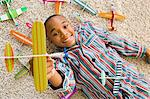 Boy lying indoors playing with toy aeroplanes Stock Photo - Premium Royalty-Free, Artist: Blend Images, Code: 6114-06613481