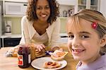 Woman and girl eating in kitchen Stock Photo - Premium Royalty-Free, Artist: Photocuisine, Code: 6114-06613489