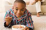 Boy lying in living room eating cereal Stock Photo - Premium Royalty-Free, Artist: urbanlip.com, Code: 6114-06613490