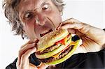 man eating double cheeseburger Stock Photo - Premium Royalty-Free, Artist: Ikon Images, Code: 6106-06614365
