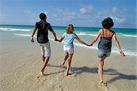 Mother and teenagers running to ocean Stock Photo - Premium Royalty-Freenull, Code: 6106-06614628
