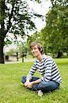 Portrait of happy young man sitting on grass at park Stock Photo - Premium Royalty-Free, Artist: Blend Images, Code: 698-06615414
