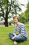 Portrait of young man sitting on grass smiling at park Stock Photo - Premium Royalty-Free, Artist: Robert Harding Images, Code: 698-06615415