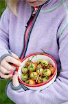 Mid section of a little girl holding bowl full of cherry tomatoes Stock Photo - Premium Royalty-Free, Artist: Blend Images, Code: 698-06615471