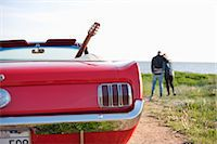 Close-up of red car with couple in background on field Stock Photo - Premium Royalty-Freenull, Code: 698-06615486