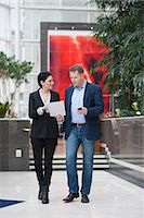 Full length of businessman with female colleague discussing paperwork while walking in office Stock Photo - Premium Royalty-Freenull, Code: 698-06615513
