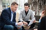 Happy businessmen going through paperwork in office Stock Photo - Premium Royalty-Free, Artist: Blend Images, Code: 698-06615514