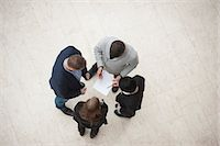 Directly above shot of four businesspeople in meeting Stock Photo - Premium Royalty-Freenull, Code: 698-06615519