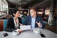 Mature businessman and female colleague with paperwork at cafe table Stock Photo - Premium Royalty-Freenull, Code: 698-06615530