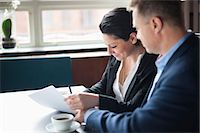 Businessman looking at woman signing contract in cafe Stock Photo - Premium Royalty-Freenull, Code: 698-06615531