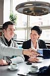 Business people shaking hands in a cafe meeting Stock Photo - Premium Royalty-Free, Artist: Mitch Tobias, Code: 698-06615537