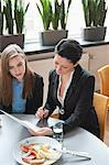 Businesswomen signing contract at table in restaurant Stock Photo - Premium Royalty-Free, Artist: Cultura RM, Code: 698-06615544